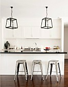 Lantern-style lamps and industrial-look metal stools at breakfast bar in black and white fitted kitchen