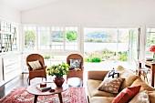 Sofa mit Kissen und Rattanstühle um Couchtisch im 50er Jahre Stil vor Fensterfront, Blick durch offene Terrassentür auf den See