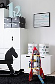 Modern, child's bedroom with robot and rocking horse in front of white, modern cupboard modules