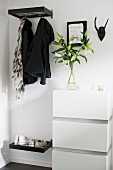 Open-plan cloakroom - jackets hanging from hooks below shelf next to white chest of drawers