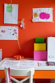 Colourful cardboard storage boxes on desk below child's drawings on orange wall