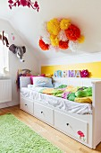Bed with white wooden frame and drawers in child's attic bedroom