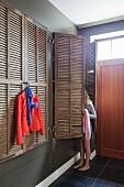 Einbauschränke mit alten Fensterladentüren, roter Blazer auf Bügel und Mädchen bei der Kleiderwahl