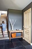 Vorraum mit heller Holztür in anthrazitfarbener Wand und dunklen Fliesen, Mädchen auf Treppenaufgang