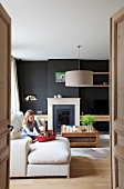 Girl with toy boat on sofa in modern living room with black-painted wall