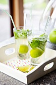 Summer drinks with lime wedges and mint leaves in glasses on wooden tray