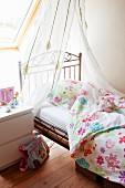 Zarter Vorhang über verspieltem Kinderbett aus Metall und Bezüge mit stilisiertem Blumenmuster