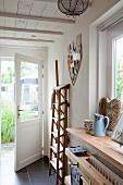 Folded wooden stepladder in foyer with open door