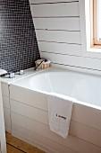 Ausschnitt einer Badewanne mit weisser Holzverkleidung an Frontseite, teilweise dunkle Mosaikfliesen und weisse Holzverkleidung an Wand