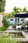 Narrow courtyard garden of terraced house with pond, table, chairs, parasol and shed at far end