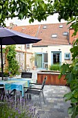 Table and chairs under parasol on paved patio of terraced house garden with pond
