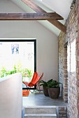 View of Butterfly armchair and potted plant in renovated interior with rustic character