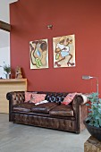 Brown, vintage leather couch below artworks on red-brown wall in modern interior