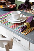 White breakfast place setting with linen napkin and striped place mat