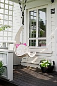 White hanging chair suspended from veranda roof of white wooden house
