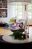 Candlesticks on coffee table in front of swivel easy chairs with scatter cushions; artworks on wall in background