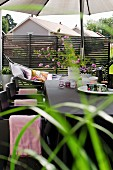 Cups, tealight holders and bouquet of garden flowers on table below parasol on terrace; hammock in background