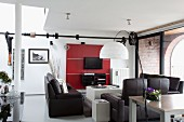 Lounge area with black leather sofa set opposite flatscreen TV and shelves on red wall-mounted panels in loft-style apartment