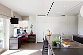 Moderner Wohnraum - Essbereich mit Küchenblock, dunkle Steinplatte, im Hintergrund weisser Einbauschrank, in Zimmerecke Frau am Arbeitstisch vor Fenster