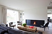 Loungebereich mit Panoramafenster in modernem Ambiente, graue Sessel und Klassikerstuhl im Retro Look um rustikale Bodentische aus Vierkanthölzern vor Kaminfeuer