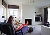 Woman sitting on chaise longue and dog on floor in cosy atmosphere in front of open fire in modern interior