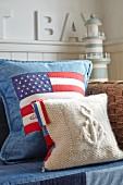 Stars and stripes cushion on sofa with miniature lighthouse in background
