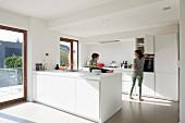 weiße Designer Küche mit minimalistischem Flair, kleines Kind auf Küchenblock sitzend gegenüber Mutter vor Hängeschrank