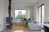 Hellgraues Ecksofa in moderner Lounge-Ecke, Mutter und Kind auf gelbem Flokatiteppich beim Spielen