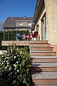 Summer day - steps leading to wooden terrace with family sitting on garden chairs