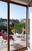 View through open terrace door of mother and children sitting on wooden terrace on summer day