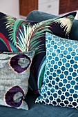 Various scatter cushions with patterns of geometric shapes and plant motifs on sofa