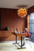 Child sitting at minimalist desk under classic pendant lamp in room with 60s-style wall panelled in rosewood