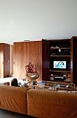 Gemütliche, braune Ledercouch in Loungebereich, Kind beim Fernsehen, Einbauschrank aus Palisanderholz mit Fernseher hinter offener Tür