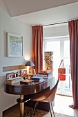 Abgerundeter Schreibtisch und Holzschalen Stuhl im Retro-Look vor Fenstertür mit bodenlangem Vorhang