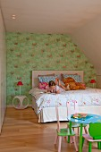 Child's attic bedroom, girl on double bed, table and small chairs in foreground painted pink and green