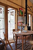 Old wooden furniture and vase of protea in dining area in house with many reclaimed elements