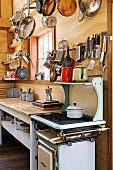 Simple kitchen in weekend house with small gas cooker and pans hung from rack