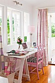 White desk and pink chair below window