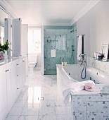 Marble floor tiles, washstand with white base units and glazed shower area in spacious, bright bathroom