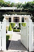 White garden gate below climber-covered pergola and gravel path leading through front garden to Colonial-style country house in sunlight