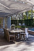 Set table on spacious wooden terrace below striped awning with view of sunny garden
