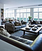 Various leather and grey velvet sofas around coffee table in open interior with white French windows