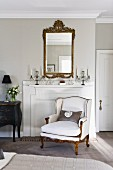 Elegant, white Rococo-style reading chair in front of fireplace with wooden surround in traditional interior