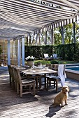 Dog sitting in front of set table on wooden terrace below striped awning and view into sunny garden
