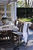 Festively set table on wooden terrace and towel draped over chair on summer day