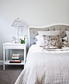 Table lamp on white bedside table next to French bed with pillows stacked against upholstered headboard in traditional bedroom painted pale grey