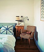 Fifties-style armchair next to bedside table and double bed in corner of bedroom