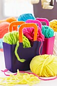 Balls of brightly coloured wool in purple plastic bags with wool-wrapped handles