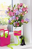 Bouquet of purple freesias and eustomas in vase wrapped in colourful woollen yarn