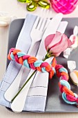 Cutlery, linen napkin and flower wrapped in napkin ring made from plaited woollen yarn